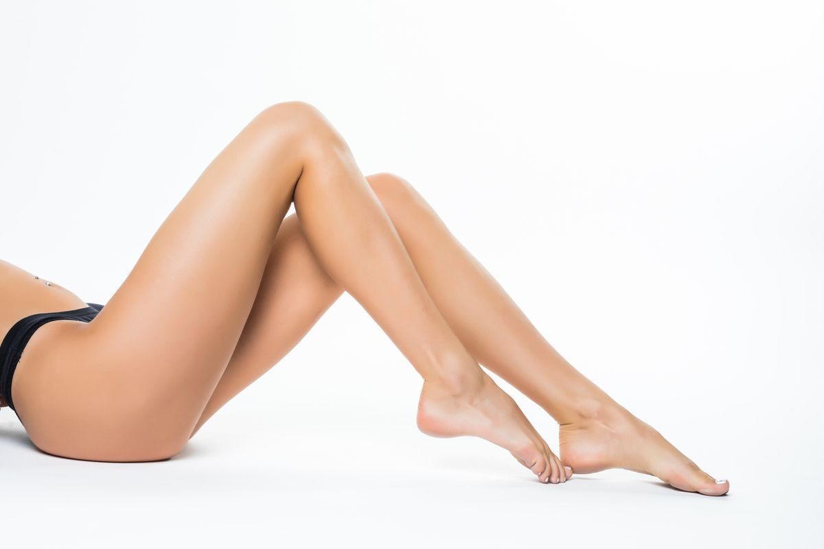 Beautiful female legs, ass back body isolated over white background. lying on the floor with long leg, Beauty spa and skin care concept.